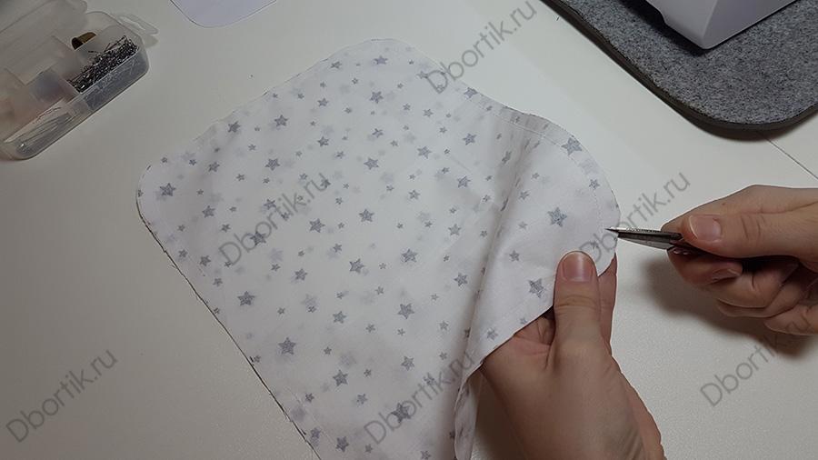 На столе лежит текстильная деталь, будущая подушка. Делается надрез с помощью ножниц, не доходя на строчки.
