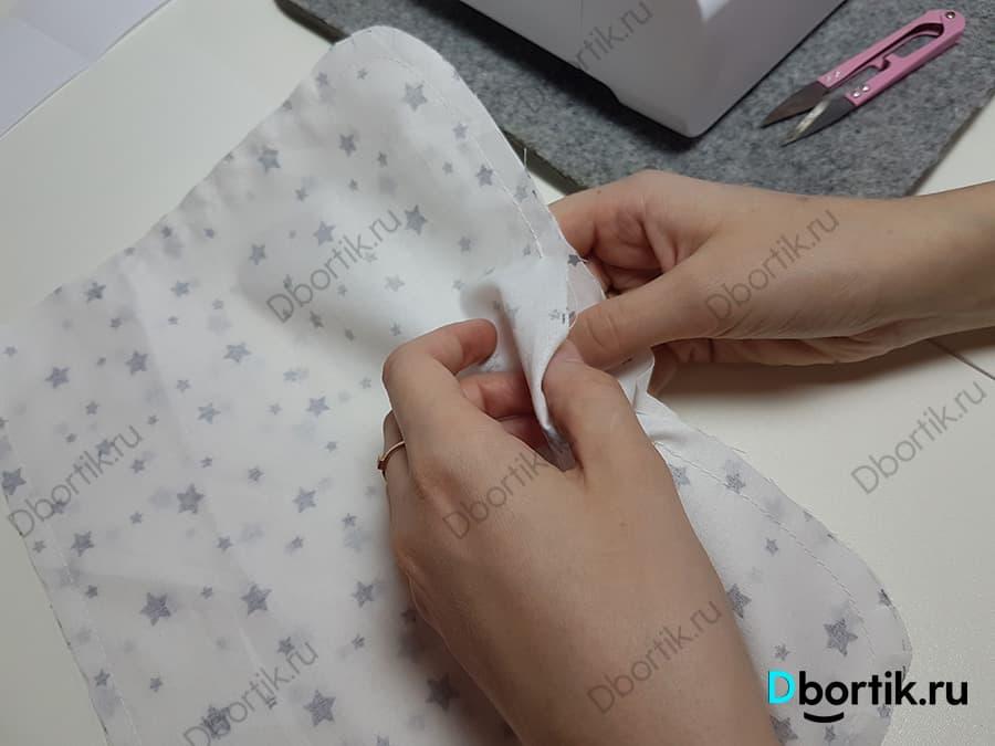 Пальцы руки выворачивают текстильное изделие для будущей подушки для кормления малы из раннее, сделанного разреза.