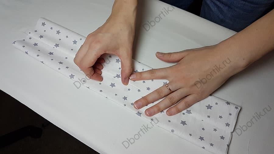 Пальцами рук расправляется шов по середине ленты.