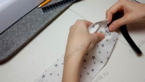 Пальцы рук вставляют булавку, которая прикреплена к резинке, в ленту для крепления подушки, для кормления малыша.