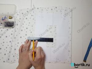 На столе кусок ткани сложенный, на нем лежит выкройка. По линейке отмеряется припуск от самого шаблона в 1 см.