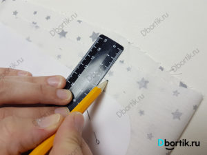 Крупный план фото, линейка и карандаш, показывает отступ, припуск от края шаблона выкройки, шаблона.