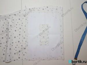 На столе хлопковая ткань, к которая закреплена выкройка с помощью иголок.