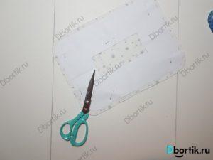 на столе лежат ножницы, вырезанный кусок ткани и шаблон.