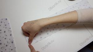 Палец руки указывает на край ткани, где необходимо сделать отступ при пошиве на машинке. Отступ в 1 см от края, другими словами ширина шва 1 см.