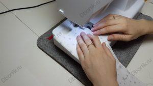 Изображение швейной машинки, руки просовывают текстильную ленту, осуществляется пошив с краю изделия.