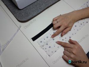 Пальца руки указывают на два места, на ленте. С боков от резинки необходимо проложить строчку на швейной машине.