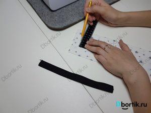 Линейка и карандаш с отметками в 1.1 см от середины шва ленты.