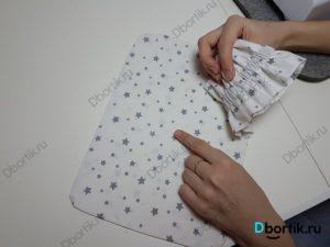 Палец указывает на середину подушки. Другая рука держит ленту.