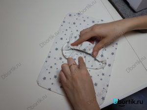 Пальцы руки держат ленту на резинке, крепление подушки. На другйо руке указательный палец, указывает на место, где необходимо приколоть иголки.