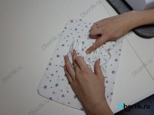 Указательный палец указывает на противоположную сторону ленту, где необходимо приколоть иголками.