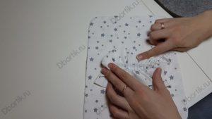 Палец руки, указывает на прикрепленные иголки, и место, где необходимо прошить.