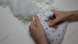Вид сверху. Руки держат подушку. Одна рука придерживает угол и разминает его, распределяя холлофайбер. Другая рука набивает холлофайбер.