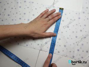 На столе отрезок ткани, руки держат измерительную ленту. Размеры, ширина 22 см.
