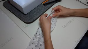 Руки протягивают черную резинку в ранее отшитый кармашек ленты. Конец резинке без булавки утоплен внутрь ленты на 1 см.