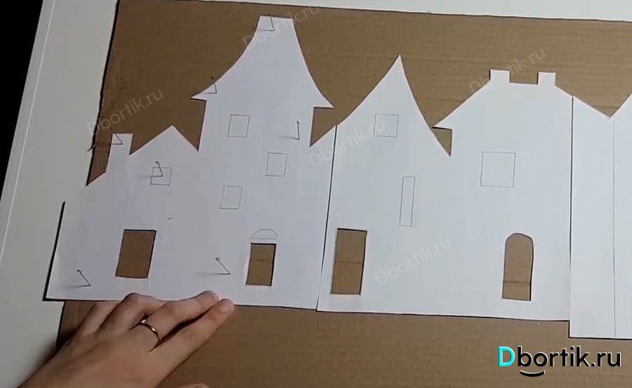 Бумага, вырезанный шаблон закреплен на картоне с помощью булавок.