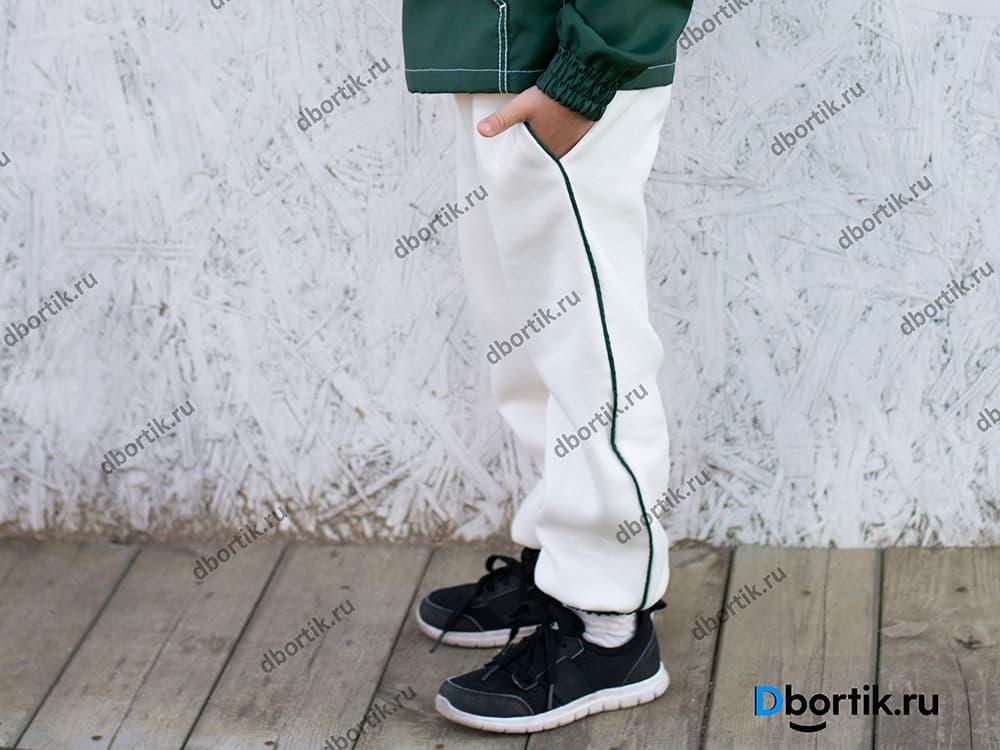 Детские спортивные штаны в готовом виде, сшитые по выкройке. Штаны белого цвета, зеленый кант и резинка.
