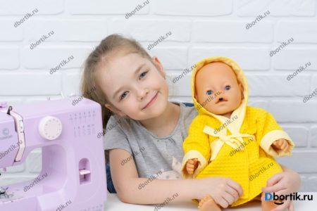 Анюта и кукла в желтом халате с капюшоном.