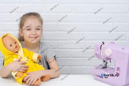 Маленькая швейная машина и кукла в желтом халате
