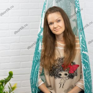 Девушка сидит в подвесных качелях кокон. Крупный план.