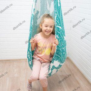 Ребенок катается на подвесных качелях кокон.