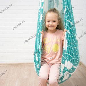 Девочка сидит в подвесных качелях кокон.