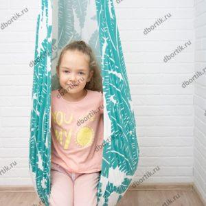 Девочка сидит в подвесных качелях кокон. Общий план.