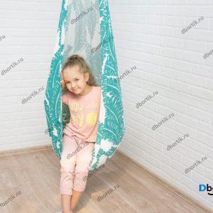 Девочка катается на подвесных качелях кокон. Дальний план.