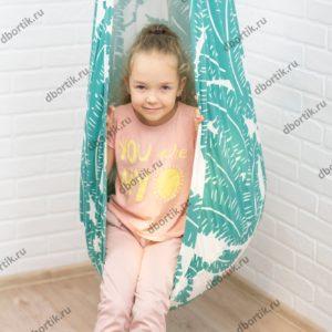 Девочка катается на подвесных качелях кокон. Крупный план.