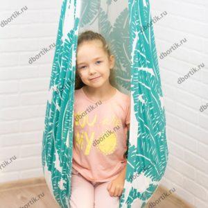 Ребенок сидит в подвесных качелях кокон. Крупный план.
