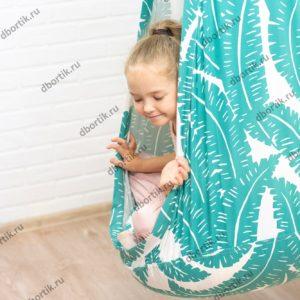 Качели вид сбоку. Ребенок катается на качелях кокон.