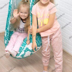 Дети играют с качелями кокон.
