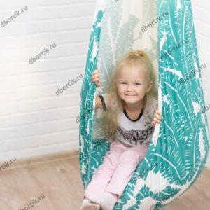 Маленький ребенок катается на подвесных качелях кокон. Вид сбоку.