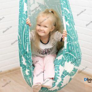 Маленький ребенок катается на подвесных качелях кокон. Крупный план.