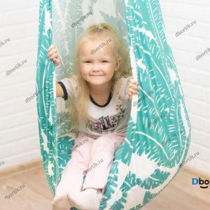 Маленький ребенок катается на подвесных качелях кокон.